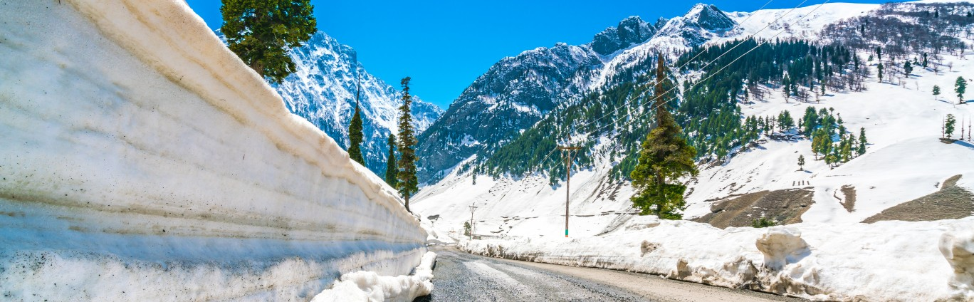 A Road surrounded by moutains with snow and trees in between