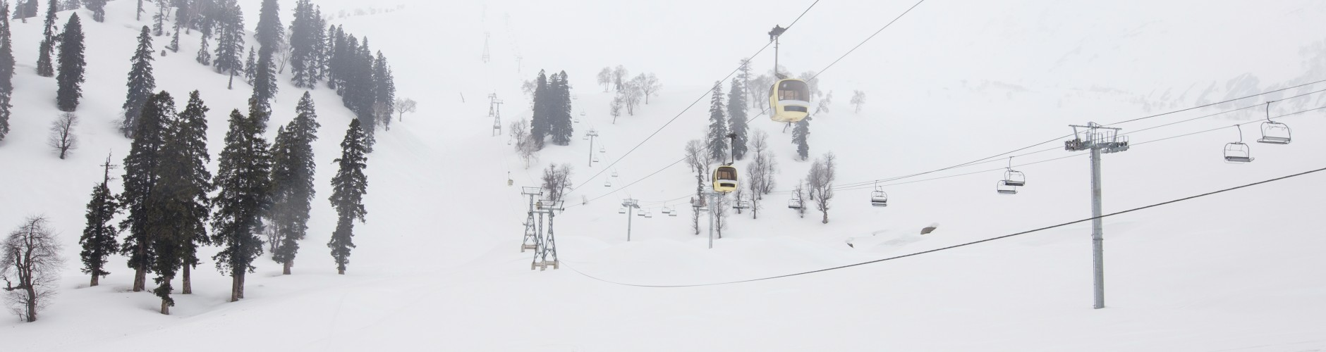 Ice mountains with few trees and two rope cars